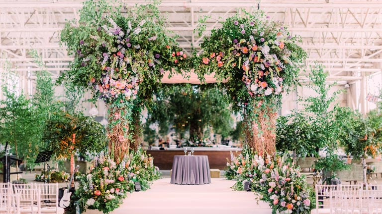 A massive green chuppah bursting with flowers and foliage inside an airport hangar for a luxury Jewish wedding